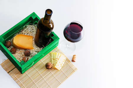 A bottle of red wine with a glass and a piece of cheese. Standard-Bild