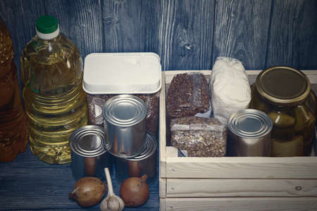 canned food and various cereals on a wooden shelf, food crisis Standard-Bild