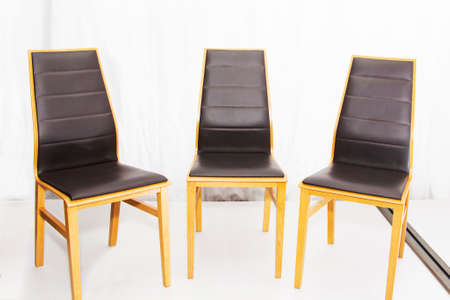Three modern new wooden chairs with leather seats in the workshop.