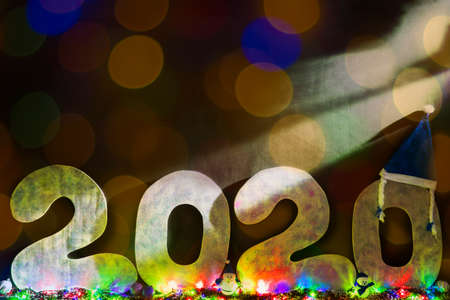 Happy new year 2020 isolated on black background with copy space for text, for holiday card. Blurred snowflakes, snow.
