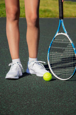 A tennis player with a racket stands on the tennis court. Sport
