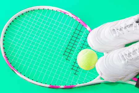 Tennis racket with a ball and sneakers, on a bright background. Photographed in the Studio.