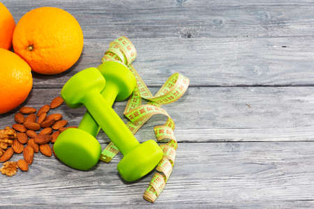Lots of oranges, dumbbells, measuring tape on a wooden textured background. Fitness, sports nutrition