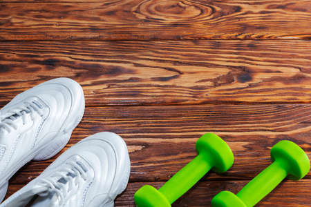 running shoes and dumbbells on a wooden background. Healthy lifestyle