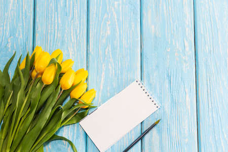 the concept of Mothers Day, the eighth of March, Valentines Day. tulips flower and notepad for writing on a wooden background