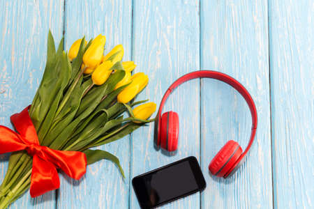 Yellow tulips in a vase with red headphones and a telephone. the concept of romantic music.
