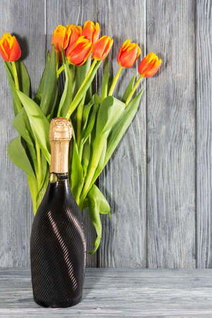 a bottle of champagne and Tulip flowers. the holiday is March 8, mothers Day. Romantic setting. Imagens