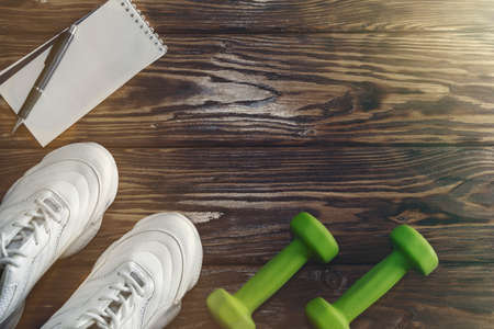 running shoes, a Notepad for recording and dumbbells on a wooden background. Healthy lifestyle Imagens