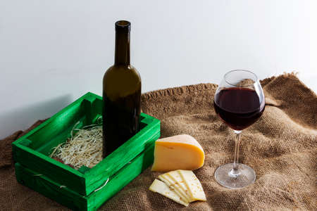 A bottle of red wine with a glass and a piece of cheese. Imagens