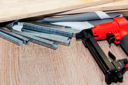 concept of furniture production and repair. Stapler and staples, working tool Imagens