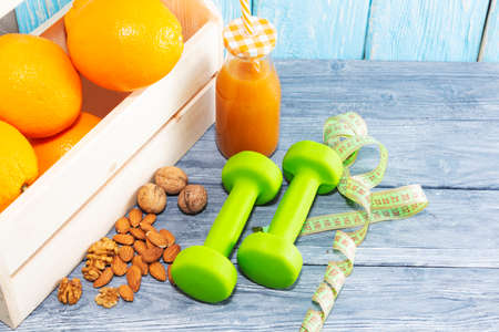 Lots of oranges and a bottle of juice, measuring tape on a wooden textured background. Fitness, sports nutrition