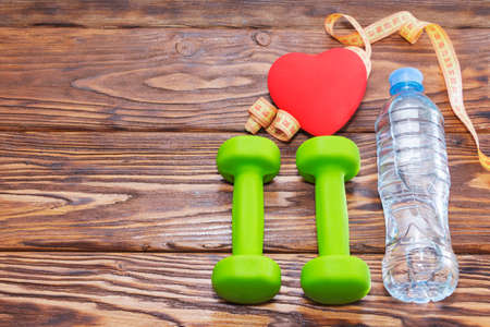 Dumbbells and a red heart on a wooden background. The concept of a healthy lifestyle