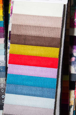 A set of fabric samples for furniture finishing. Multicolored upholstery stripes.