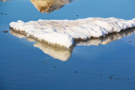 Close-up of a large piece of ice in blue water. Global warming, melting glaciers.