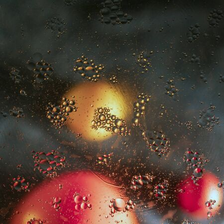Magic drops of oil dissolved in water on a blurred background with fruit.