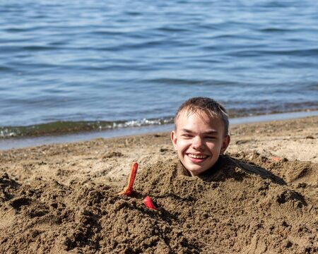 In the photo buried in a sand on the neck of a pretty boy. The photo was taken on the shores of Lake Uvilda in Chelyabinsk region, Russia.