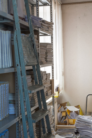 rack arrangement: A vertical image of archive in which mess. A folding ladder on foreground. Main focus on mess.