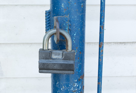 Gray padlock in the closed state on the blue fence. Close-up. Stock Photo