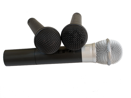 argent: Isolated image of three microphones. The big one with a white metal head and two smaller ones with black metal heads.