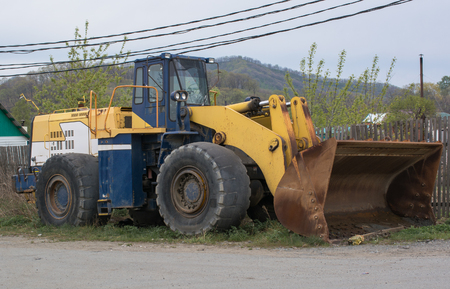 forgotten: Forgotten dozer with worn tires and a rusty bucket stands on the street