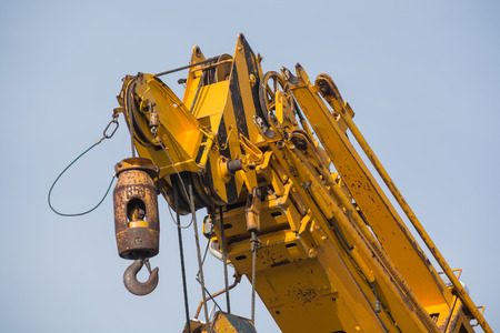lading: Yellow crane arm with hook close-up
