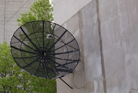 airwaves: Black antenna dish on the wall of house