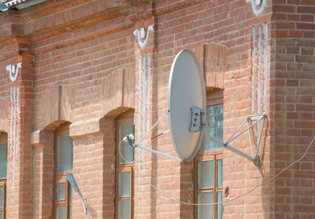 sattelite: White satellite dish on a brick wall.
