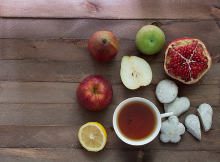 garnets: Garnets, apples, lemon, cookies and a cup of tea on a wooden table