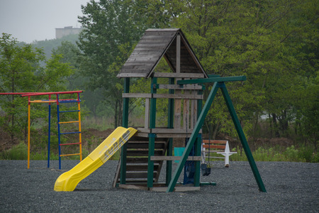 Bacground: Wooden children slide. Trees on the bacground. Stock Photo