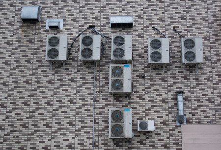 without windows: A lot of air conditioners placed on the brick wall without windows