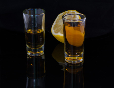 two and a half: Two glasses filled with alcohol drink and a half of a lemon