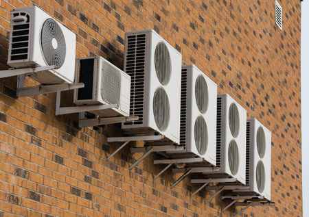 without windows: A row of air conditioners placed on the brick wall without windows
