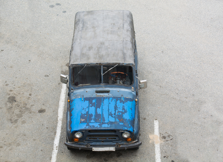 russian car: Old russian car with shabby blue paint stay on parking. A canvas top. Stock Photo