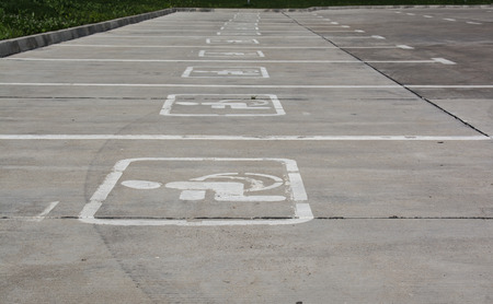 specifically: Several Parking spaces specifically for disabled people. White signs on gray concrete area.