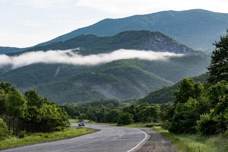 myst: Narrow road leads through the mountains where the fog lies