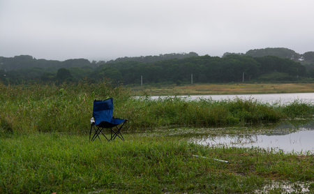 Abandoned blue camping chair on the lake shore surround by grass and reeds