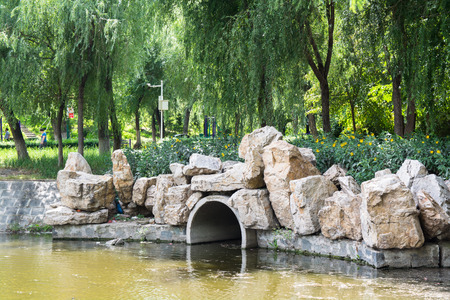 consist: Dam with drain pipe located in the public garden. Dam decor consist from flowers and boulders. Stock Photo