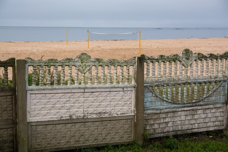impair: Old-fashioned fence along beach. Fence has intricate decor.