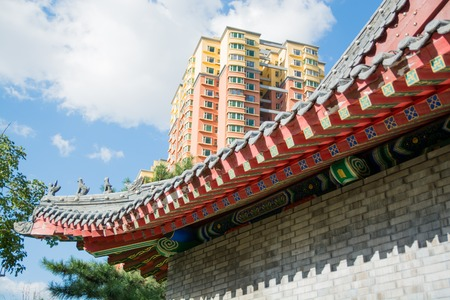 cornice: Cornice of traditional chinese roof and part of contemporary building. Colorful clay roof on background of high-rise building.