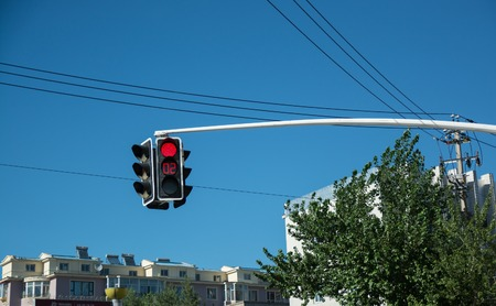 building regulations: Traffic light showing red signal and time counter. Traffic light hanging over the road with buildings on background. Stock Photo