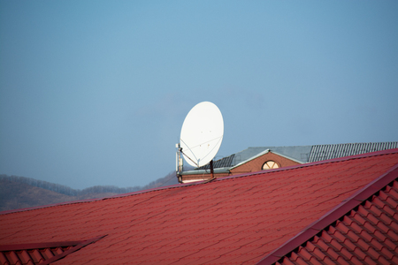 White satellite antenna mounted on the roof ridge. Minimalistic image.