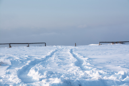 passageway: Trail of wheels on the snow surface. Track which go to the passageway between wooden railings. Stock Photo