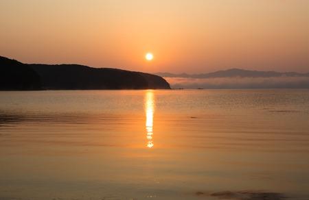 Sunset above the calm sea. Coast line and mist on the horizon.