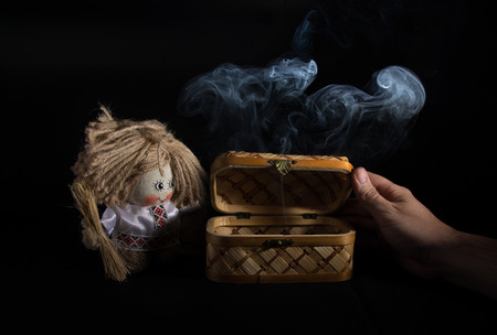 rag doll: Still life with a casket and rag doll. Black background and the smoke. Stock Photo