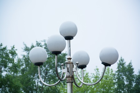 plafond: Top side of the lamp post with round plafonds. Green trees on background.