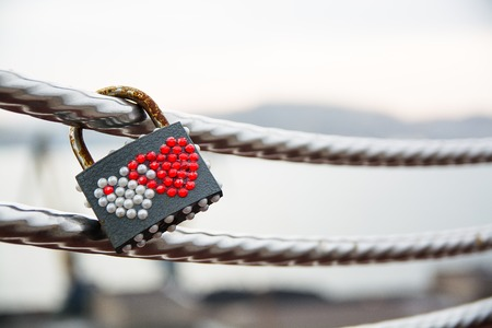 Wedding lock decorated by hearts hanging on a handrail. Symbol of marriage.