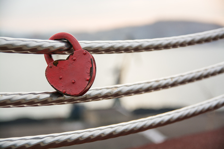 Wedding lock in shape of heart on a handrail. Symbol of marriage. Stock Photo