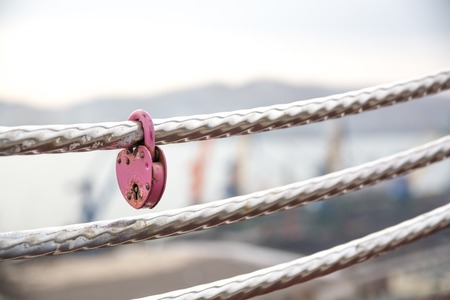 love declaration: Wedding lock in shape of heart on a handrail. Symbol of marriage. Stock Photo