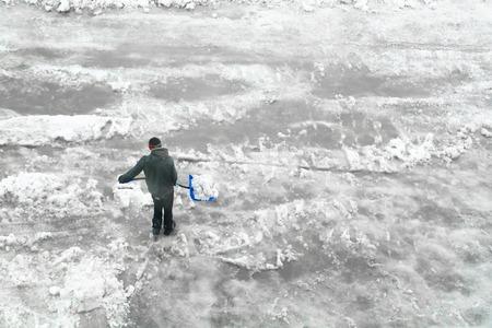 shoveling: Man shoveling snow. Minimalistic image. Top view