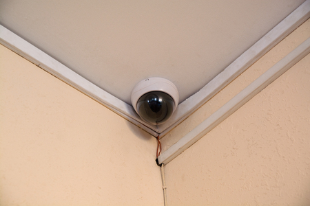 security monitor: Security camera monitor in office building. Spherical CCTV under ceiling.